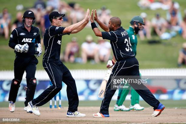 Jeetan Patel of New Zealand celebrates his wicket of Hashim Amla of South Africa with Mitchell Santner during game four of the One Day International...
