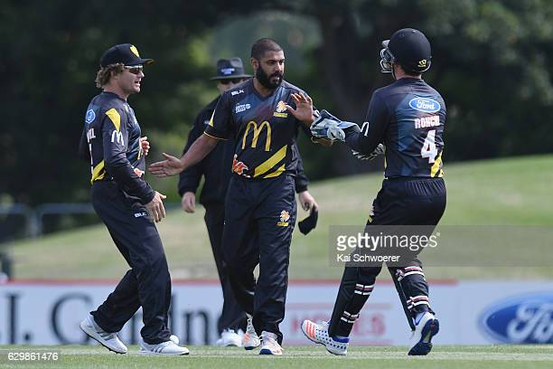 Jeetan Patel of the Firebirds is congratulated by Hamish Marshall and Luke Ronchi after dismissing Tom Latham of the Kings during the McDonalds Super...