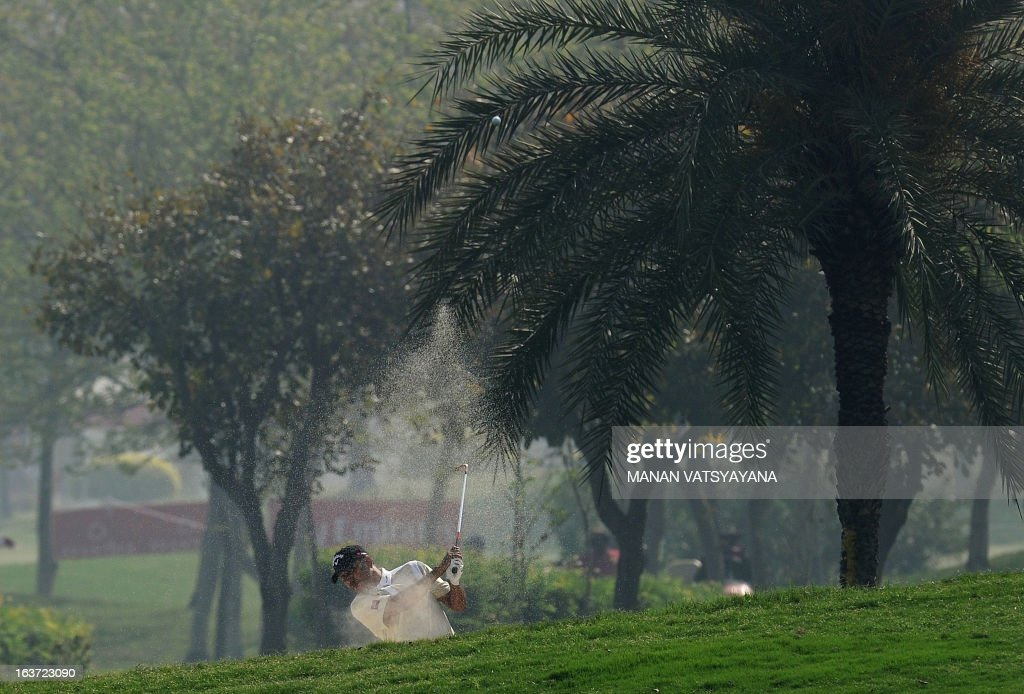 Jeev Milkha Singh of India hits the ball out of a bunker during the Avantha Masters golf tournament in Greater Noida, on the outskirts of New Delhi, on March 15, 2013. AFP PHOTO/ MANAN VATSYAYANA