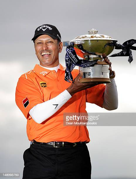 Jeev Milkha Singh of India poses with the trophy after winning a playoff against Francesco Molinari of Italy on the 18th green during the final round...