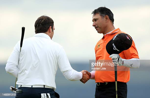Jeev Milkha Singh of India shakes hands with Francesco Molinari of Italy after winning a playoff on the 18th green during the final round of the...