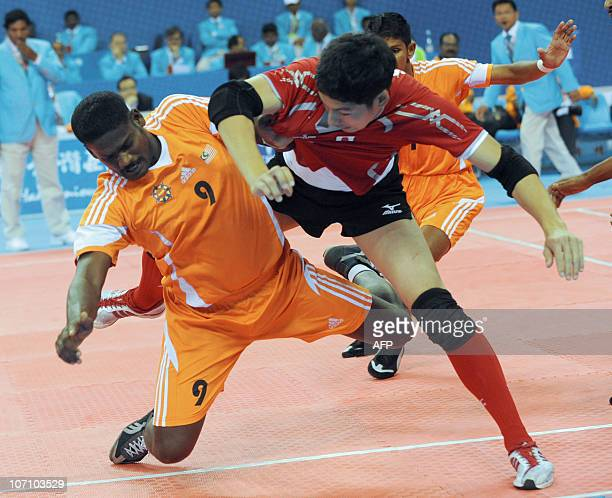Jeevan Raman of Malaysia tries to bring down Hiromi Takahashi of Japan during the kabaddi men's group B round 3 match at the 16th Asian Games in...