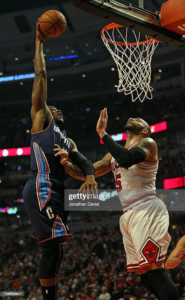 Jeff Adrien #4 of the Charlotte Bobcats dunks the ball over Carlos Boozer #5 of the Chicago Bulls at the United Center on December 31, 2012 in Chicago, Illinois.