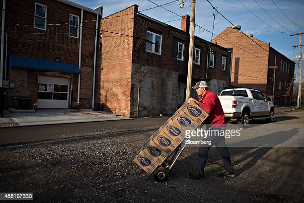 Jeff Allen a delivery driver for Brewers Distributing Co pushes cases of Bud Light as he delivers AnheuserBusch beer to Maquet's Rail House in Pekin...