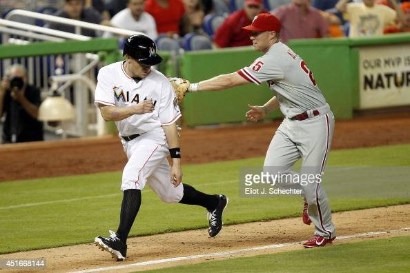 Jeff Baker of the Miami Marlins is tagged out in a rundown by Cody Asche of the Philadelphia Phillies in the eighth inning at Marlins Park on July 3...