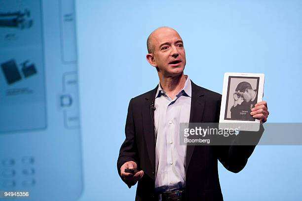 Jeff Bezos chairman president and chief executive officer of Amazoncom Inc holds an Amazoncom Kindle DX electronic reader during a news conference in...
