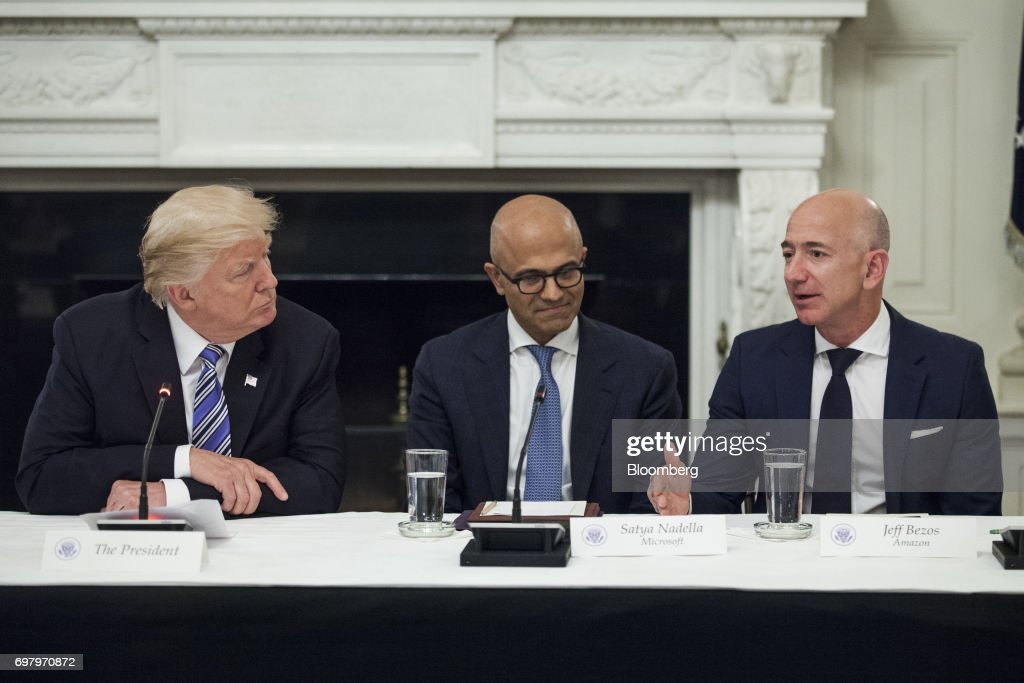 Jeff Bezos, president and chief executive officer of Amazon.com Inc., right, speaks as U.S. President Donald Trump, left, and Satya Nadella, chief executive officer of Microsoft Corp., listen during the American Technology Council roundtable hosted at the White House in Washington, D.C., U.S., on Monday, June 19, 2017. Executives from many of the world's largest technology companies gathered for the first meeting of the American Technology Council with Trump and his senior advisers. Photographer: Zach Gibson/Bloomberg via Getty Images