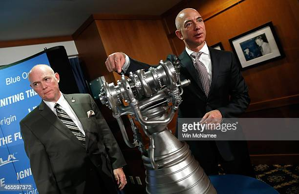 Jeff Bezos the founder of Blue Origin and Amazoncom gestures toward a model of the new BE4 rocket engine during a press conference with Tory Bruno...