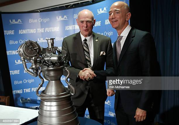 Jeff Bezos the founder of Blue Origin and Amazoncom shake hands behind a model of the new BE4 rocket engine during a press conference with Tory Bruno...