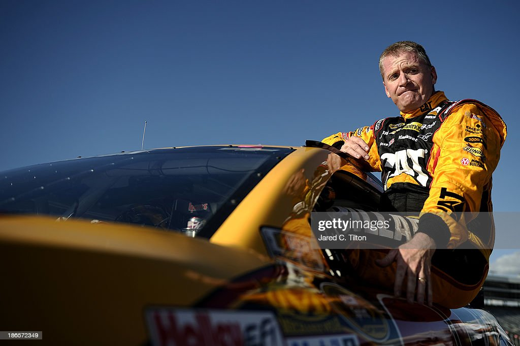 Jeff Burton, driver of the #31 Caterpillar Chevrolet, climbs from his car after qualifying for the NASCAR Sprint Cup Series AAA Texas 500 at Texas Motor Speedway on November 1, 2013 in Fort Worth, Texas.