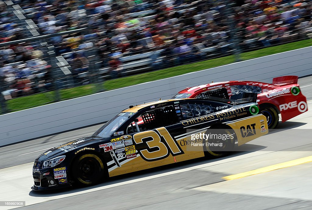 Jeff Burton, driver of the #31 Childress Institute for Pediatric Trauma Chevrolet, races Juan Pablo Montoya, driver of the #42 Target Chevrolet, during the NASCAR Sprint Cup Series STP Gas Booster 500 on April 7, 2013 at Martinsville Speedway in Ridgeway, Virginia.