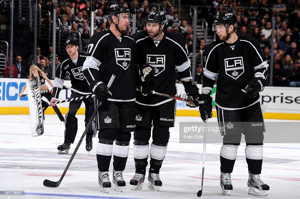 Jeff Carter #77, Dustin Penner #25, and Jake Muzzin #6 of the Los Angeles Kings talk during a break in the game against the Columbus Blue Jackets at Staples Center on February 15, 2013 in Los Angeles, California.