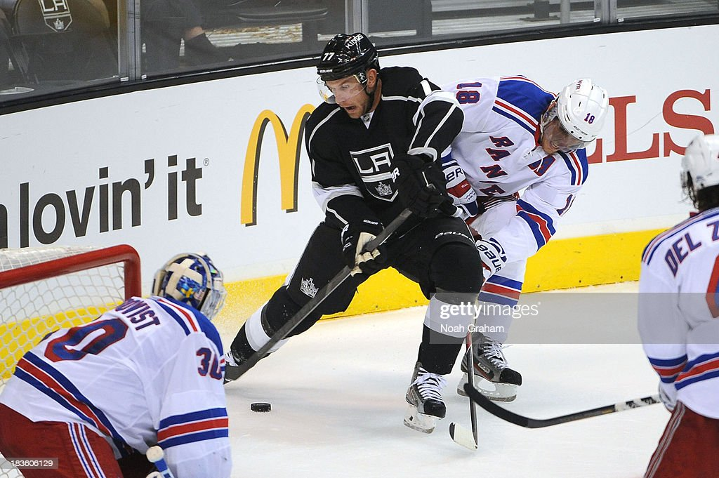 Jeff Carter #77 of the Los Angeles Kings battles for the puck against Marc Staal #18 of the New York Rangers at Staples Center on October 7, 2013 in Los Angeles, California.