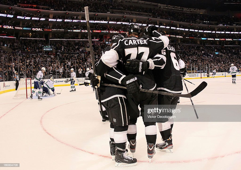 Jeff Carter #77 of the Los Angeles Kings celebrates his goal in the second period with teammates Mike Richards #10 and Jake Muzzin #6 during the NHL game against the Vancouver Canucks at Staples Center on January 28, 2013 in Los Angeles, California.