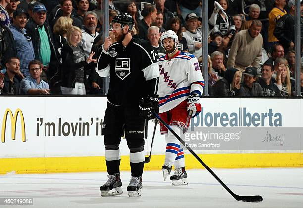 Jeff Carter of the Los Angeles Kings points to his face after being hit by Dominic Moore of the New York Rangers who received a penalty during...