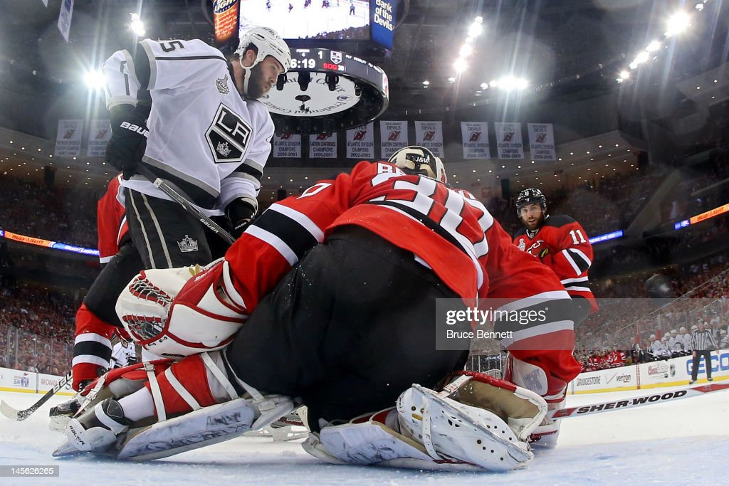 Jeff Carter of the Los Angeles Kings shoot sthe game winning goal in overtime passed Martin Brodeur of the New Jersey Devils as Dustin Penner and...
