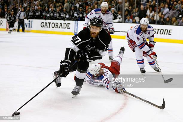 Jeff Carter of the Los Angeles Kings skates away with the puck as Ryan McDonagh of the New York Rangers falls to the ice during overtime of Game Five...