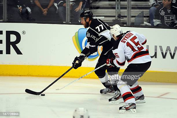 Jeff Carter of the Los Angeles Kings skates with the puck against Petr Sykora of the New Jersey Devils in Game Six of the 2012 Stanley Cup Final at...