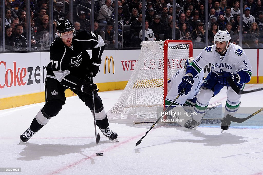 Jeff Carter #77 of the Los Angeles Kings skates with the puck against Jason Garrison #5 of the Vancouver Canucks at Staples Center on January 28, 2013 in Los Angeles, California.