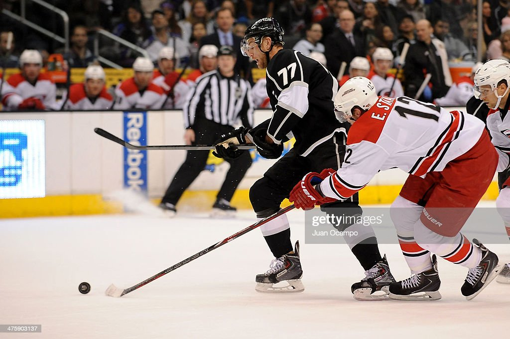 <a gi-track='captionPersonalityLinkClicked' href=/galleries/search?phrase=Jeff+Carter&family=editorial&specificpeople=227320 ng-click='$event.stopPropagation()'>Jeff Carter</a> #77 of the Los Angeles Kings skates with the puck against <a gi-track='captionPersonalityLinkClicked' href=/galleries/search?phrase=Eric+Staal&family=editorial&specificpeople=202199 ng-click='$event.stopPropagation()'>Eric Staal</a> #12 of the Carolina Hurricanes at Staples Center on March 1, 2014 in Los Angeles, California.