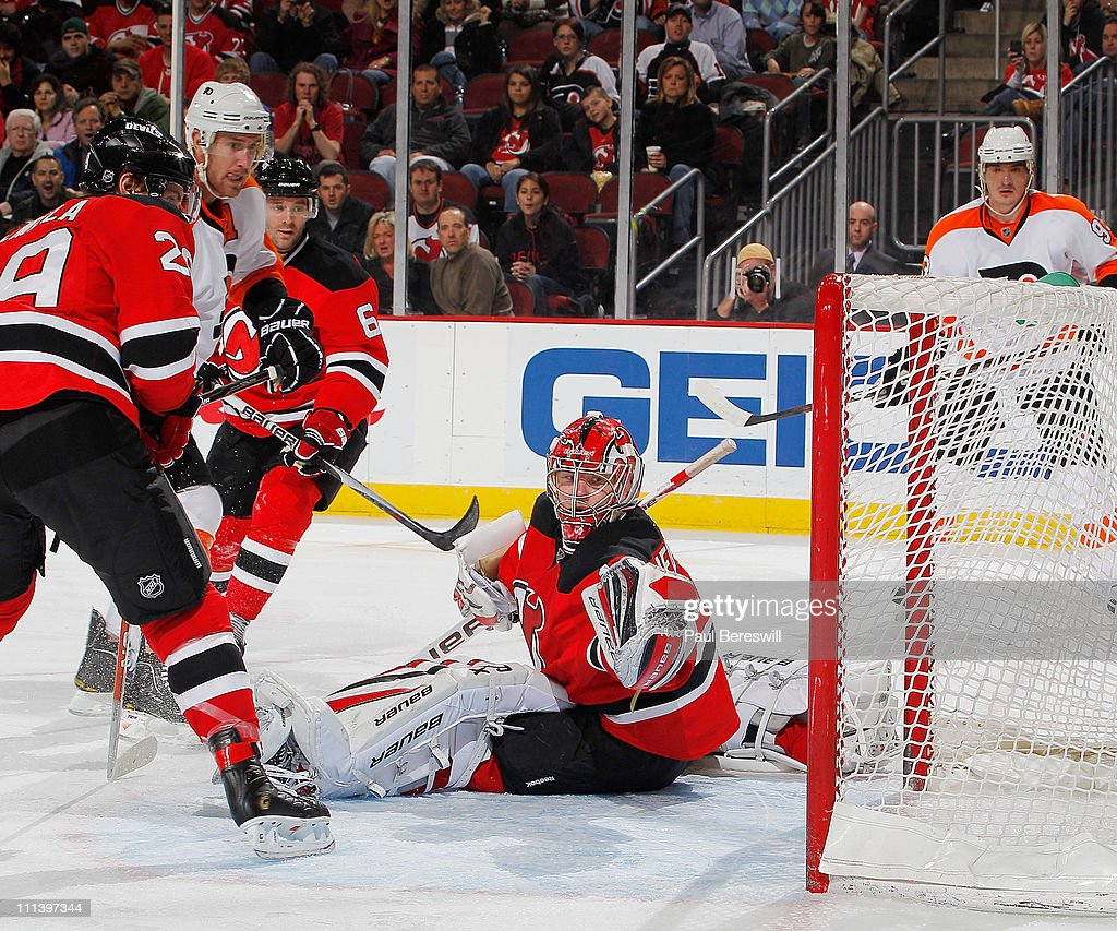 Jeff Carter of the Philadelphia Flyers shoots the puck past goalie Johan Hedberg of the New Jersey Devils as Devils Anssi Salmela and Andy Greene try...