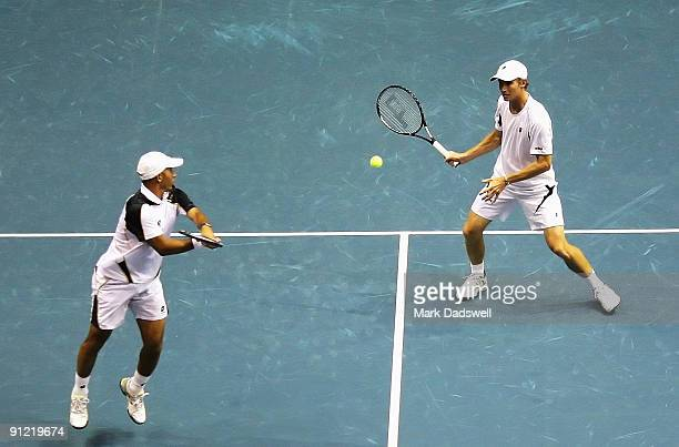 Jeff Coetzee watches as Rik De Voest of South Africa plays a volley in their doubles match with Marat Safin of Russia and Gilles Simon of France...