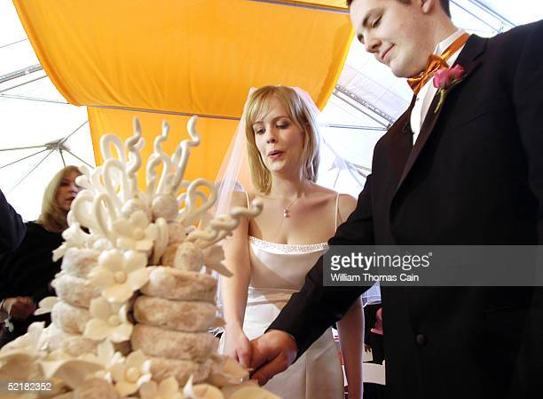 Jeff Dewald and Margaret Neary cut their donut wedding cake after their wedding at Dunkin' Donuts February 11 2005 in Philadelphia Pennsylvania The...