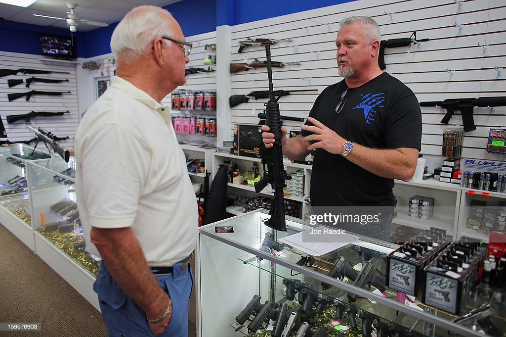 Jeff Dillard (R), a co-owner of the National Armory gun store, helps Richard Fuller with an AR-15 rifle on January 16, 2013 in Pompano Beach, Florida. President Barack Obama today in Washington, DC announced a broad range of gun initiatives that his administration thinks will help curb gun violence.