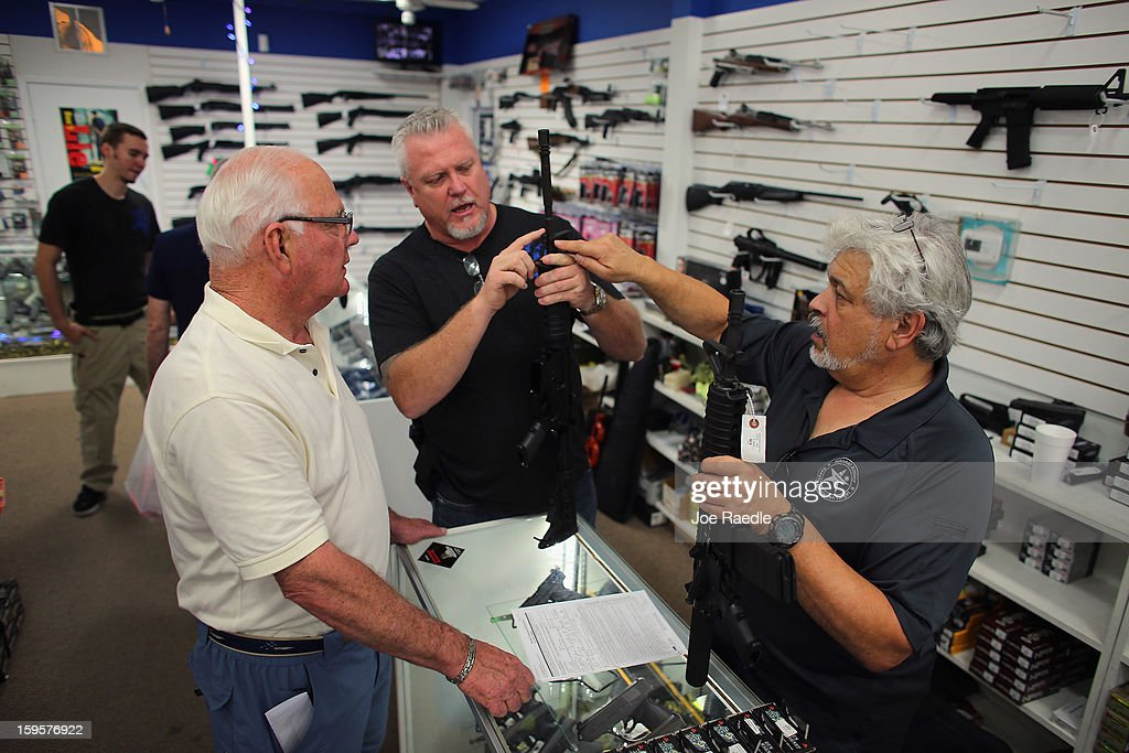 Jeff Dillard (C) and Dr. Gary Lampert (R), co-owners of the National Armory gun store, help Richard Fuller as he shops for an AR-15 rifle on January 16, 2013 in Pompano Beach, Florida. President Barack Obama today in Washington, DC announced a broad range of gun initiatives that his administration thinks will help curb gun violence.