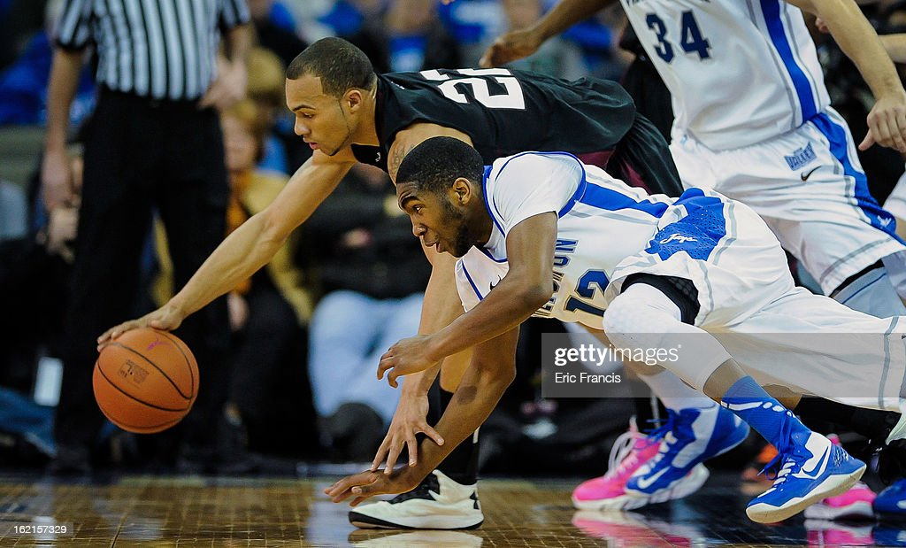 Jeff Early of the Southern Illinois Salukis and Jahenns Manigat of the Creighton Bluejays reach for a loose ball during their game at the CenturyLink...