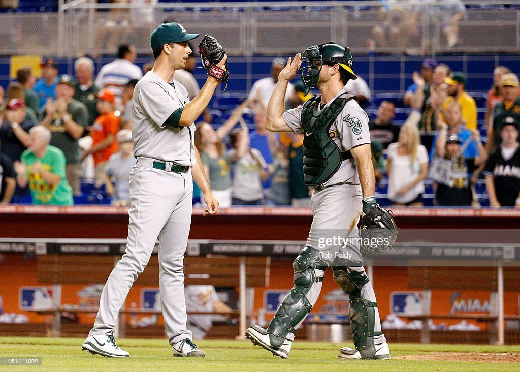 Jeff Francis of the Oakland Athletics highfives John Jaso after defeating the Miami Marlins in the game at Marlins Park on June 28 2014 in Miami...