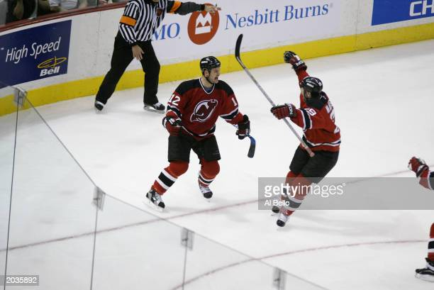 Jeff Friesen of the New Jersey Devils celebrates his game winning goal with Grant Marshall against Patrick Lalime of the Ottawa Senators during game...
