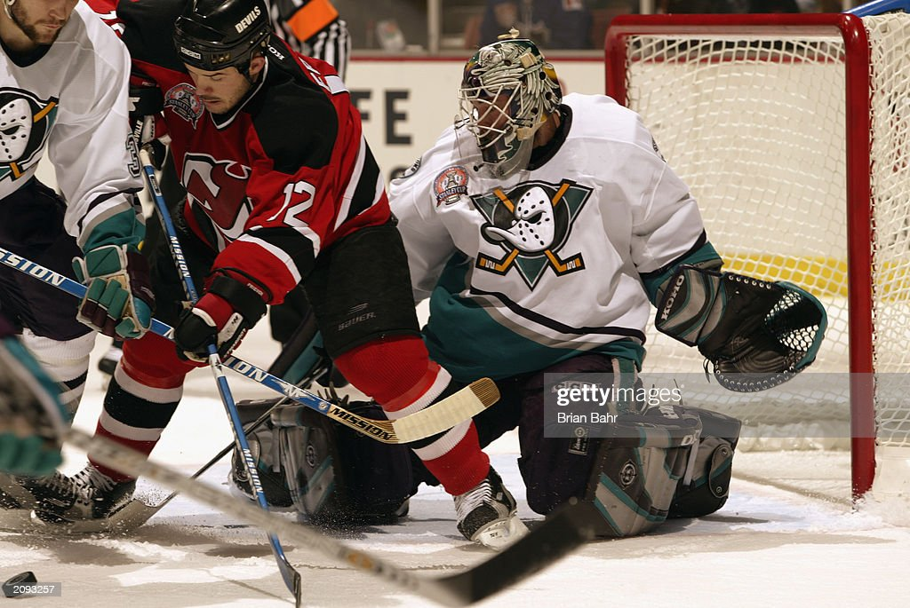 Jeff Friesen #12 of the New Jersey Devils scrambles for the puck against Keith Carney #3 of the Anaheim Mighty Ducks during Game Six of the 2003 Stanley Cup Finals at the Arrowhead Pond of Anaheim on June 7, 2003 in Anaheim, California. The Ducks won 5-2.