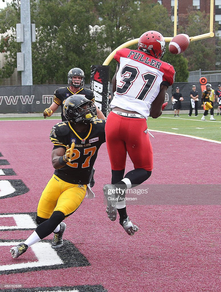 Jeff Fuller of the Calgary Stampeders looks to grab a pass in front of Delvin Breaux of the Hamilton TigerCats in a CFL game at Ron Joyce Stadium on...