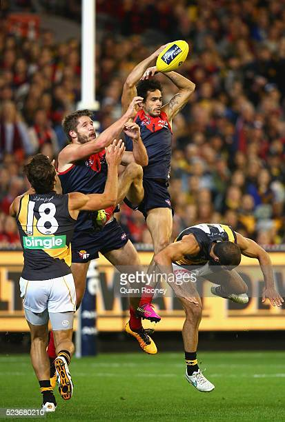 Jeff Garlett of the Demons attempts to mark over the top of Bachar Houli of the Tigers during the round five AFL match between the Melbourne Demons...