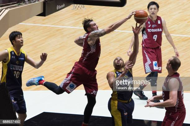 Jeff Gibbs of the Tochigi Brex is blocked by Ryan Spangler of the Kawasaki Brave Thunders during the B League final match between Kawasaki Brave...