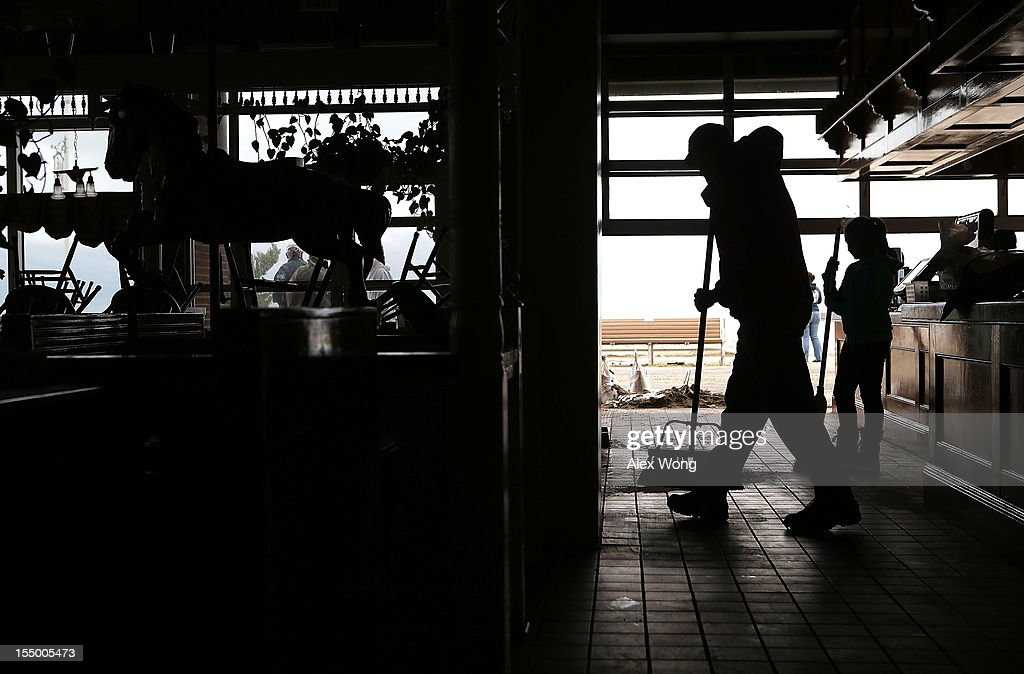 Jeff Gibbs (L), owner of The Dough Roller, cleans up the mess that was left after a flood that was caused by Hurricane Sandy with the daughter of his manager Damla Upperman, Alexa Upperman (R) October 30, 2012 in Ocean City, Maryland. The storm has claimed at least 33 lives in the United States, and has caused massive flooding across much of the Atlantic seaboard. U.S. President Barack Obama has declared the situation a 'major disaster' for large areas of the U.S. east coast, including New York City, with widespread power outages and significant flooding in parts of the city.