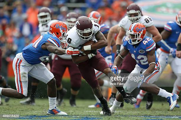 Jeff Glover of the Eastern Kentucky Colonels is taken down by Marcus Maye of the Florida Gators during the first half of the game at Ben Hill Griffin...