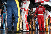 Jeff Gordon driver of the Axalta Chevrolet and fellow drivers stand under umbrellas prior to driver introductions for the NASCAR Sprint Cup Series...
