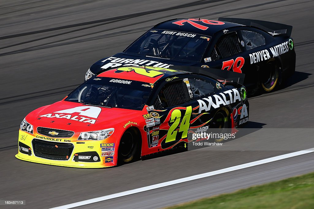 Jeff Gordon, driver of the #24 Axalta Chevrolet, and Kurt Busch, driver of the #78 Furniture Row / Denver Mattress Chevrolet, race during the NASCAR Sprint Cup Series 13th Annual Hollywood Casino 400 at Kansas Speedway on October 6, 2013 in Kansas City, Kansas.