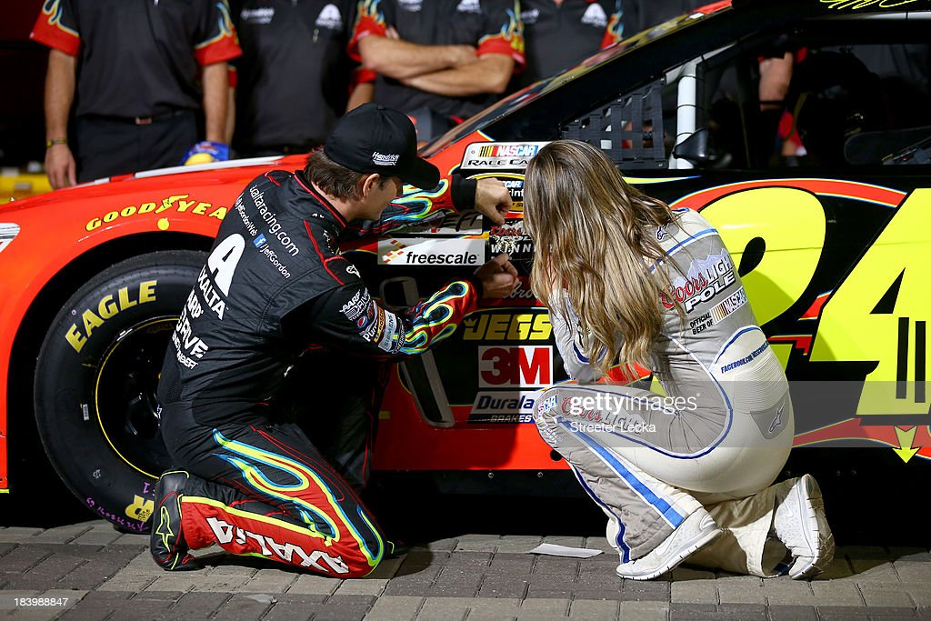 Jeff Gordon, driver of the #24 Axalta Chevrolet, and Miss Coors Light Rachel Rupert apply the Coors Light Pole Award sticker to Gordon's car after qualifying for the pole for the NASCAR Sprint Cup Series Bank of America 500 at Charlotte Motor Speedway on October 10, 2013 in Concord, North Carolina.