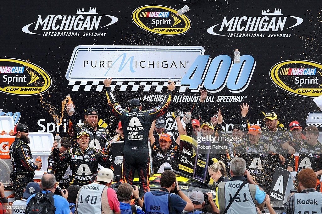 Jeff Gordon driver of the Axalta Chevrolet celebrates in Victory Lane after winning the NASCAR Sprint Cup Series Pure Michigan 400 at Michigan...