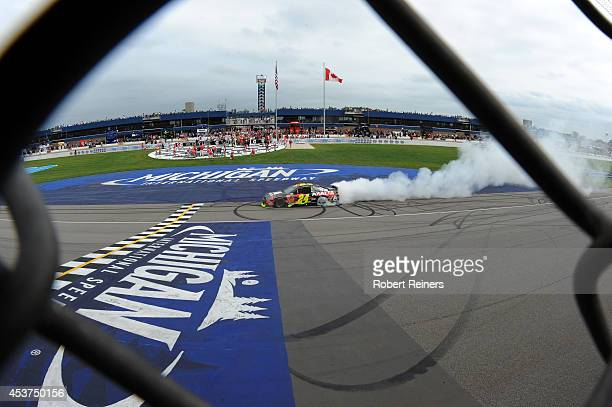 Jeff Gordon driver of the Axalta Chevrolet celebrates with a burnout after winning the NASCAR Sprint Cup Series Pure Michigan 400 at Michigan...