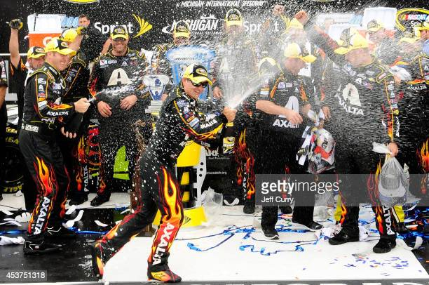 Jeff Gordon driver of the Axalta Chevrolet celebrates with champagne in victory lane after winning the NASCAR Sprint Cup Series Pure Michigan 400 at...