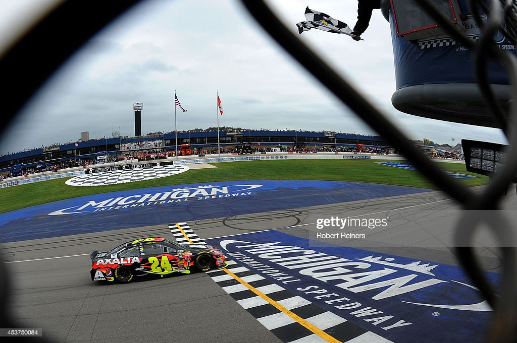 Jeff Gordon driver of the Axalta Chevrolet crosses the finish to win the NASCAR Sprint Cup Series Pure Michigan 400 at Michigan International...