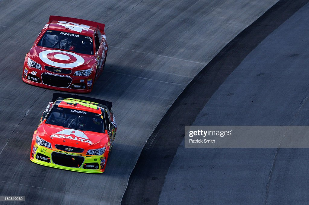 Jeff Gordon, driver of the #24 Axalta Chevrolet, leads Juan Pablo Montoya, driver of the #42 Target Chevrolet, during the NASCAR Sprint Cup Series AAA 400 at Dover International Speedway on September 29, 2013 in Dover, Delaware.
