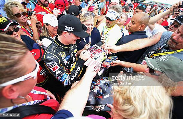 Jeff Gordon driver of the AXALTA Chevrolet signs autographs for fans during practice for the NASCAR Sprint Cup Series Ford EcoBoost 400 at...