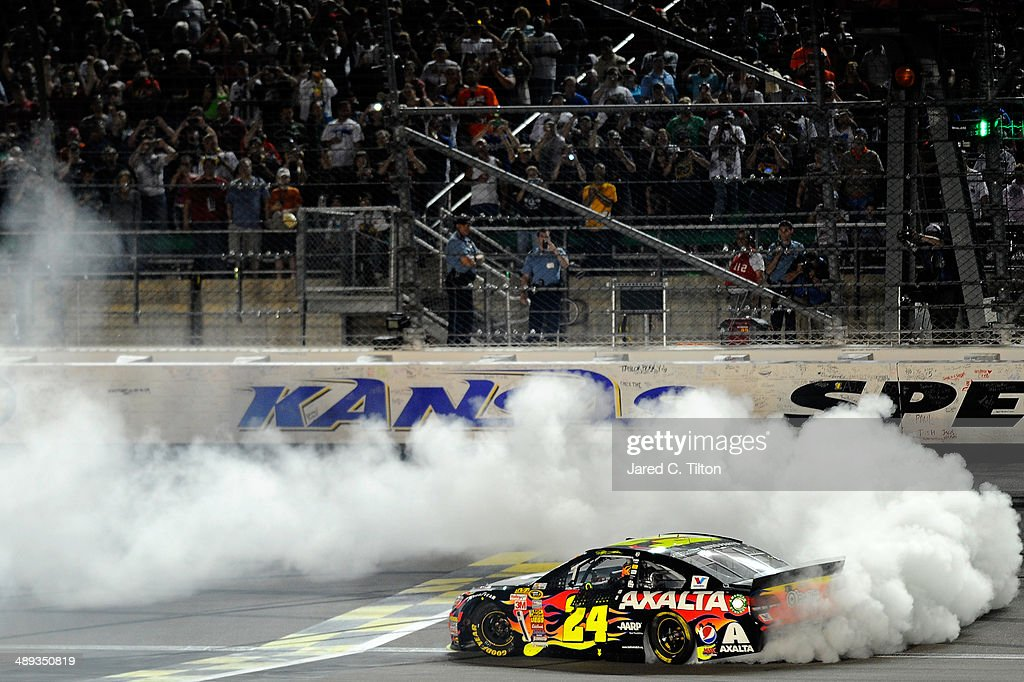 Jeff Gordon driver of the Axalta Coatings Chevrolet celebrates with a burnout after winning the NASCAR Sprint Cup Series 5Hour Energy 400 at Kansas...
