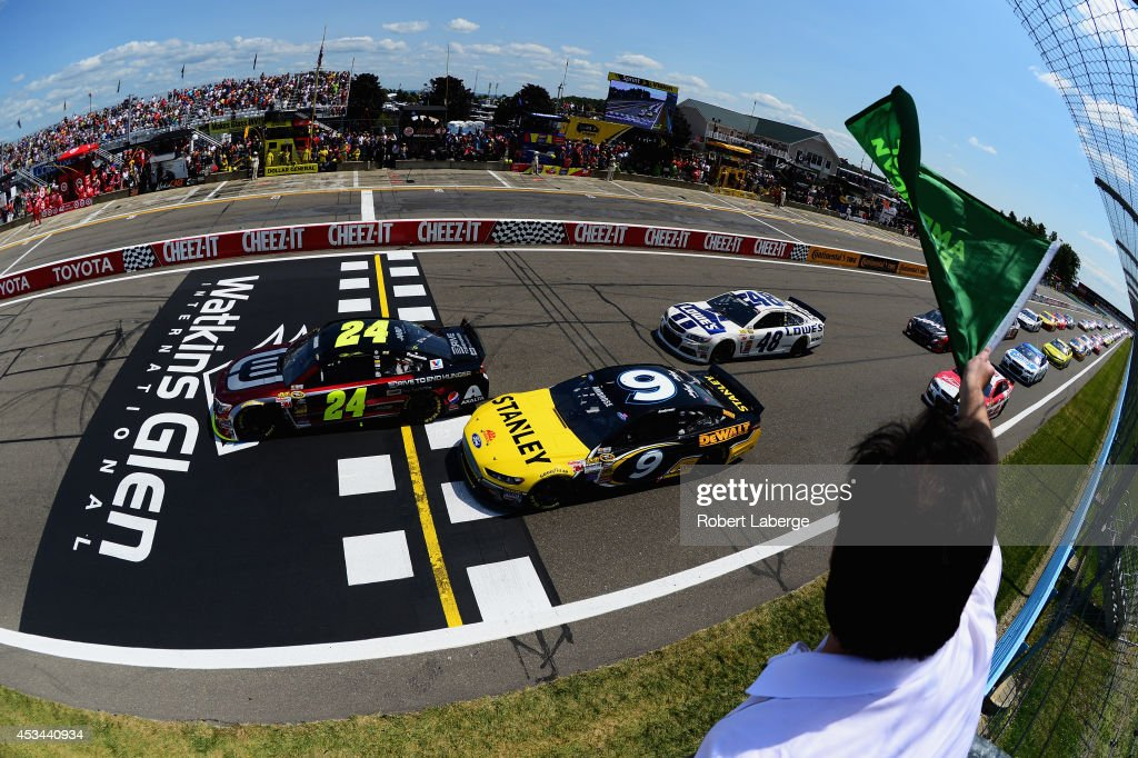 Jeff Gordon, driver of the #24 Drive to End Hunger Chevrolet, and Marcos Ambrose, driver of the #9 Stanley Ford, lead the field to the green flag for the running of the NASCAR Sprint Cup Series Cheez-It 355 at Watkins Glen International on August 10, 2014 in Watkins Glen, New York.