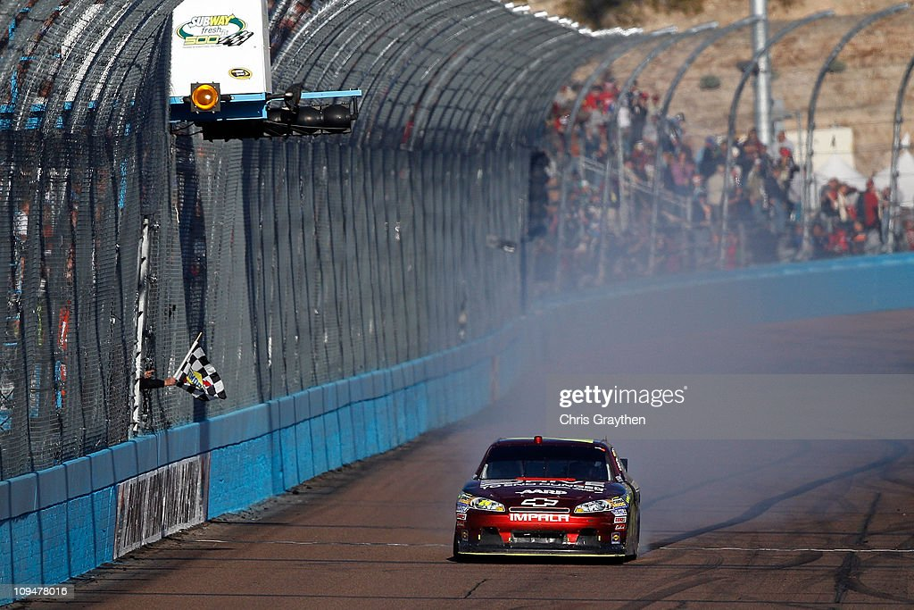 Jeff Gordon driver of the Drive to End Hunger Chevrolet celebrates after winning the Subway Fresh Fit 500 at Phoenix International Raceway on...
